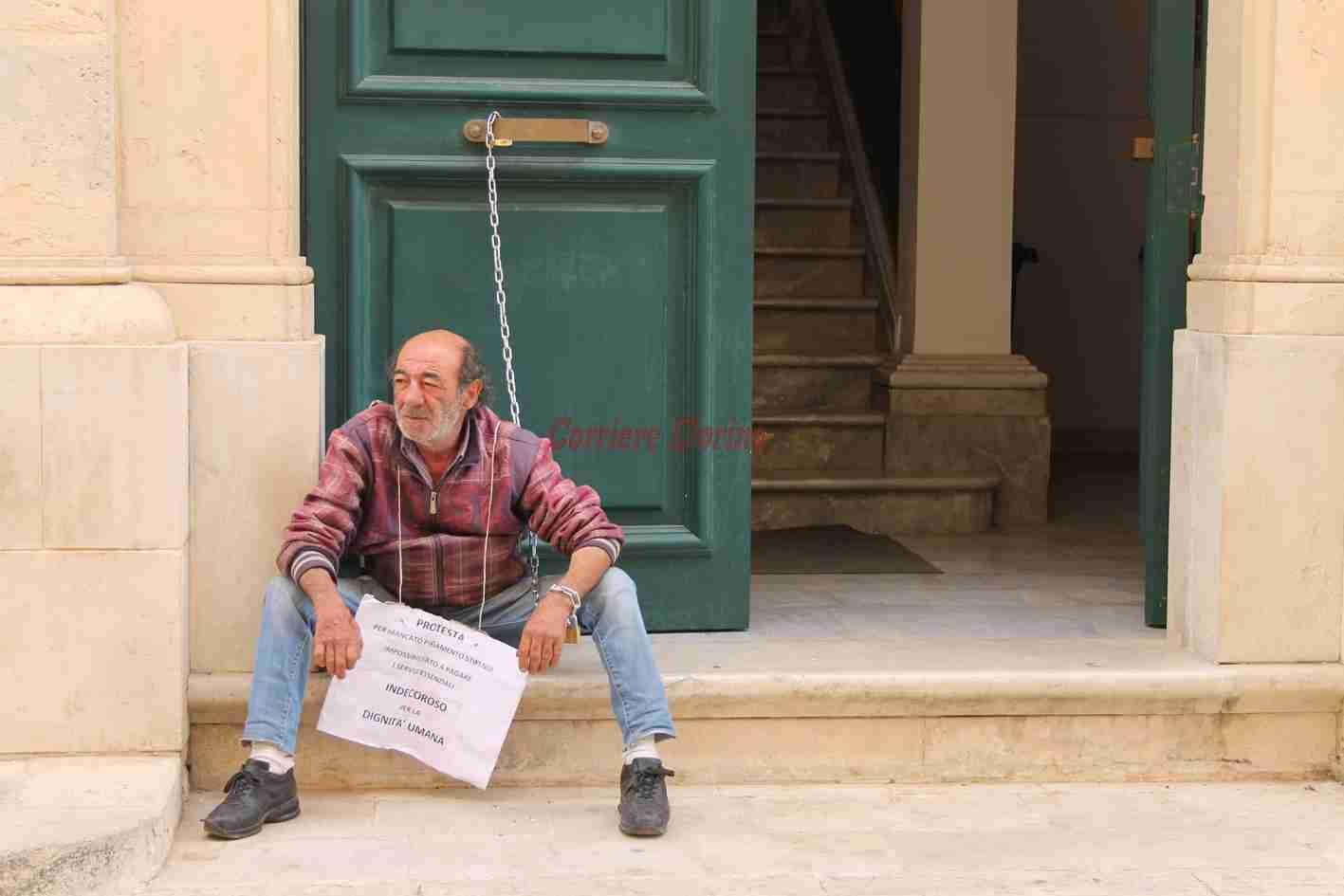 Stipendi in ritardo: dipendente comunale si incatena alla porta del Comune di Rosolini